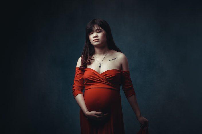 Schwangere Frau im roten Kleid stehend