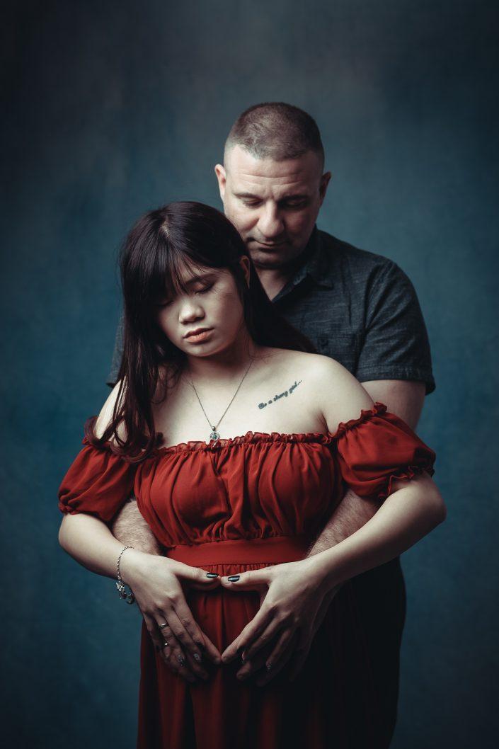 Schwangere Frau im roten Kleid mit Partner