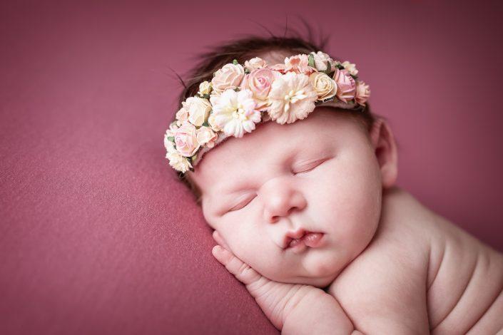 neugeborenes baby mit blumenkranz